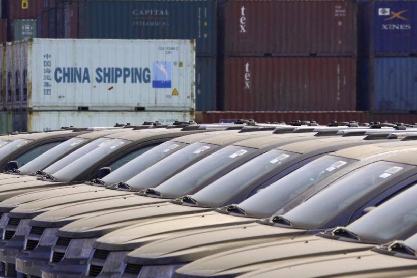 Containers can be seen stacked behind imported Buick cars, covered in dust, made by American car maker General Motors, in this picture taken March 2, 2011, at the Binhai docks area in the Chinese coastal city of Tianjin.