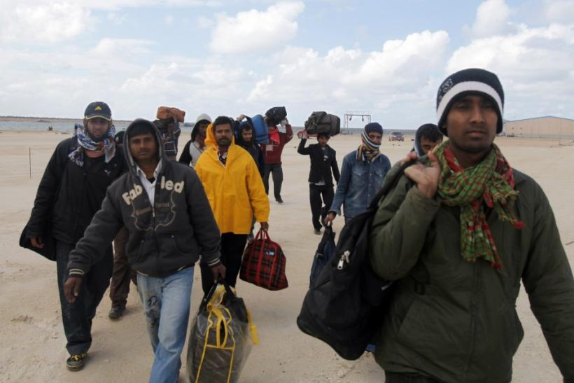 Migrant workers from Bangladesh leave the harbour in Benghazi, after failing to secure a ship to flee Libya