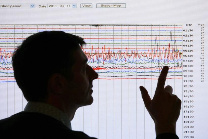 A seismologist poses points to a seismographic graph showing the magnitude of the earthquake in Japan, on a monitor at the British Geological Survey office in Edinburgh
