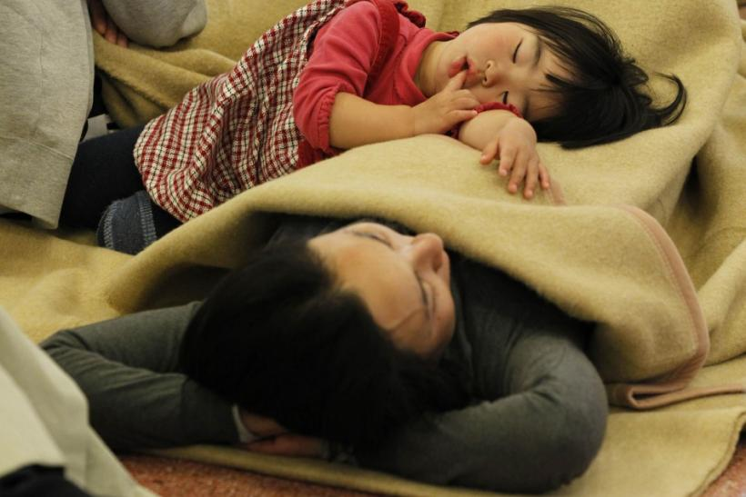 Passengers sleep at a lobby as they wait for their transportation at Haneda Airport in Tokyo