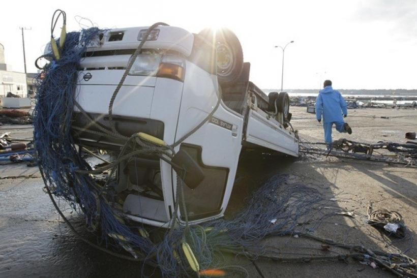 A fisherman walks past a turned over truck after a tsunami hit in Oarai town, northeast of Tokyo March 12, 2011.