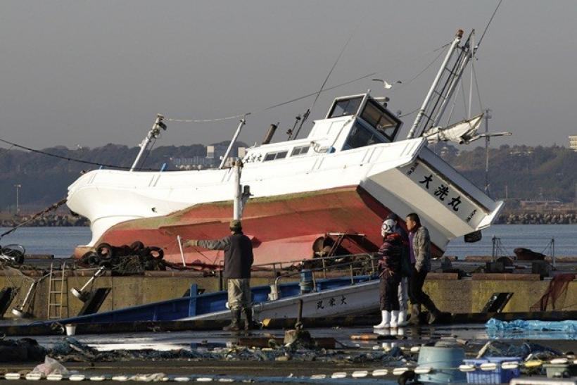 Fishermen and local residents look at fishing boats swept by a tsunami at a port in Oarai town, northeast of Tokyo March 12, 2011.