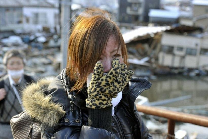 A woman cries after learning that her mother was successfully rescued from a building following an earthquake and tsunami in Miyagi Prefecture, northeastern Japan March 12, 2011.