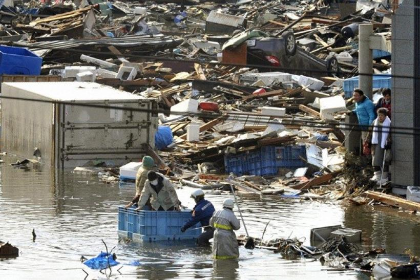 People, in a floating container, are rescued from a building following an earthquake and tsunami in Miyagi Prefecture, northeastern Japan March 12, 2011.
