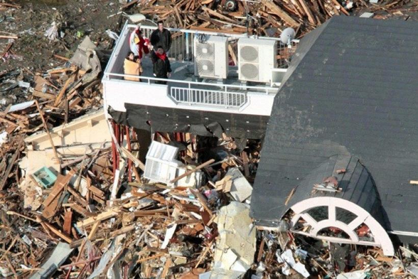 People wait for rescue on a rooftop following an earthquake and tsunami in Iwate Prefecture, northeastern Japan March 12, 2011.