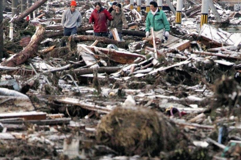 People make their way through a street clogged with debris in Sendai city, Miyagi prefecture March 12, 2011.