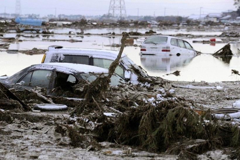 Cars are buried in mud and debris following an earthquake and tsunami in Sendai, northeastern Japan March 12, 2011.
