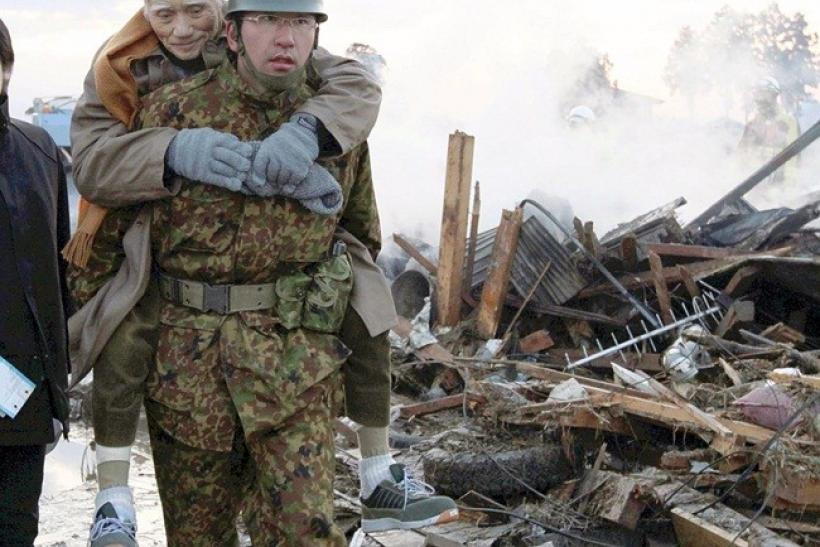 A member of the Japan Self-Defence Forces carries a man in Natori city, in Miyagi prefecture March 12, 2011.