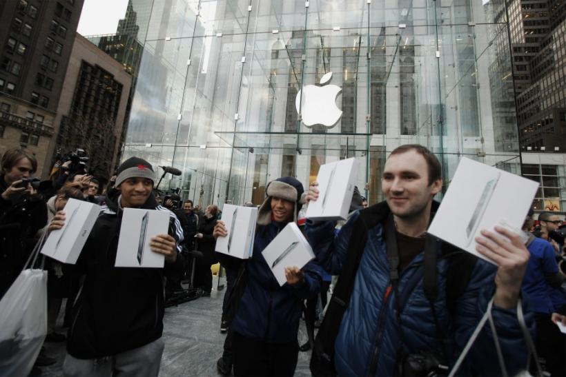Customers hold up their Apple's iPad 2 tablets after purchasing the second generation devices at the Apple's flagship 5th Ave store in New York