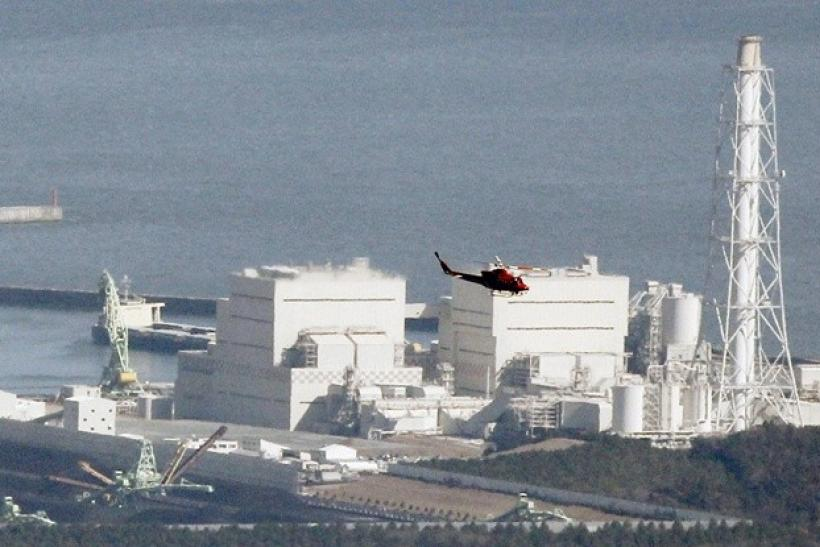 A helicopter flies past Japan's Fukushima Daiichi No.1 Nuclear reactor March 12, 2011.