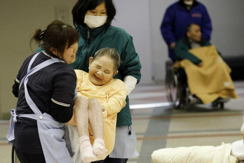 Caretakers carry a woman who is evacuated from a nursing home, which is located in the evacuation area near the Fukushima Daini nuclear plant, at a temporary shelter in Koriyama