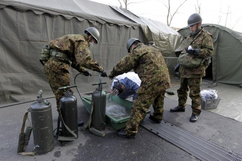 Man who was evacuated from vicinity of Fukushima's nuclear power plant washes his head at JGSDF's makeshift facility to cleanse people who might have been exposed to radiation in Nihonmatsu
