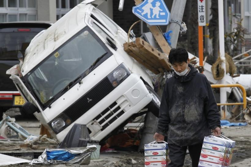A man carries boxes of tissue papers at a devastated area hit by earthquake and tsunami in Kesennuma, Miyagi Prefecture in northern Japan, March 15, 2011