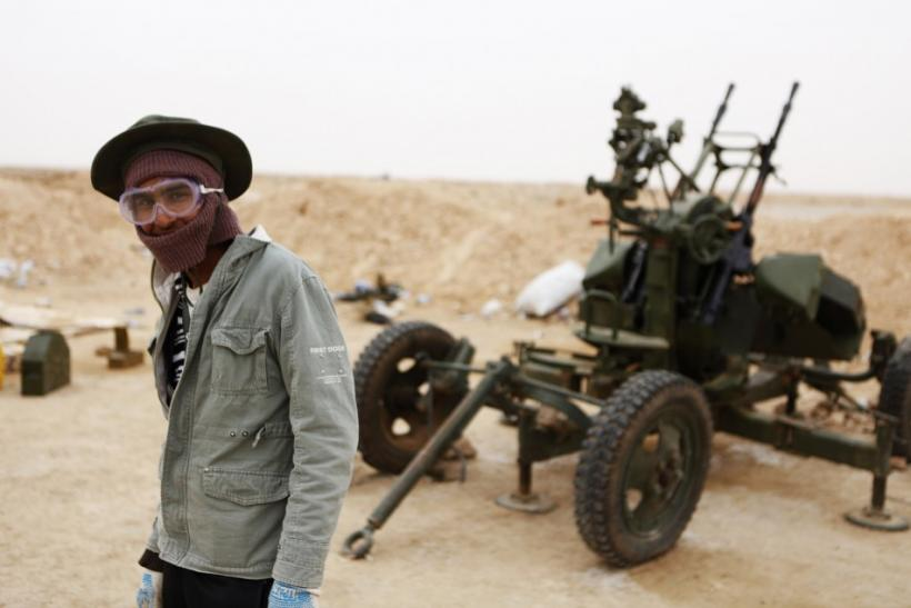 A Libyan rebel stands near an anti-aircraft gun at a checkpoint outside the city of Ajdabiyah