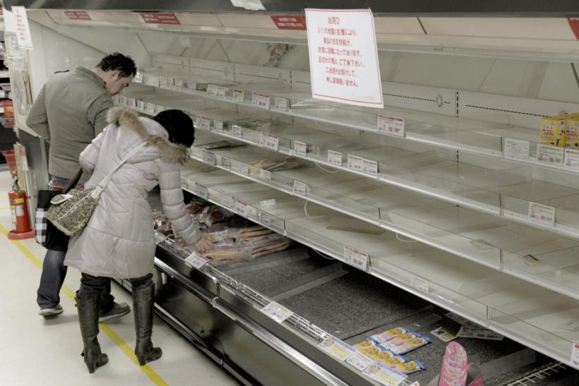 People shop for food from an almost empty shelf at a store in Tokyo
