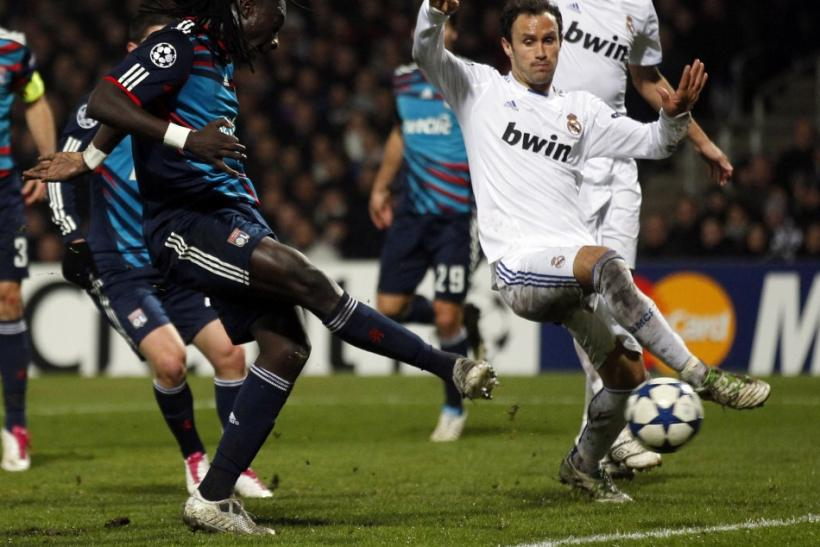 Olympique Lyon's Gomis shoots to score against Real Madrid as Real Madrid's Carvalho looks on during their Champions League soccer match in Lyon