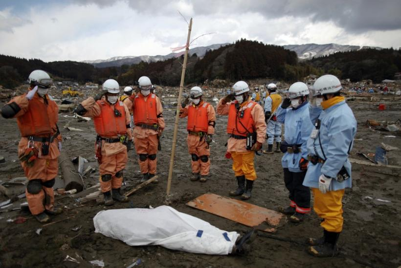 Rescue workers salute next to a body they retrieved from the rubbles in Rikuzentakat, days after the area was devastated by a magnitude 9.0 earthquake and tsunami March 17, 2011.