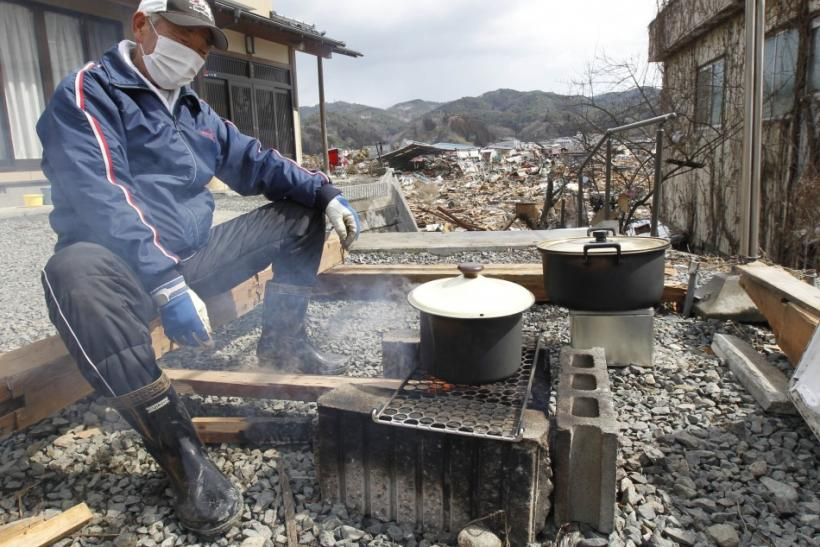 A man cooks at his home at a devastated area hit by the earthquake and tsunami in Kesennuma, north Japan, March 17, 2011.