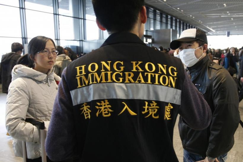 An official from Hong Kong's immigration department helps Chinese nationals to board a flight at Narita airport in Tokyo March 17 2011. China's embassy has set-up a help desk at Narita airport to help its nationals evacuate Tokyo, following last week's ea