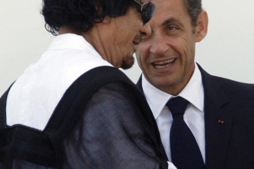 Libya's leader Gaddafi speaks with France's President Sarkozy as he leaves the final meeting at the G8 summit in L'Aquila 10/07/2009