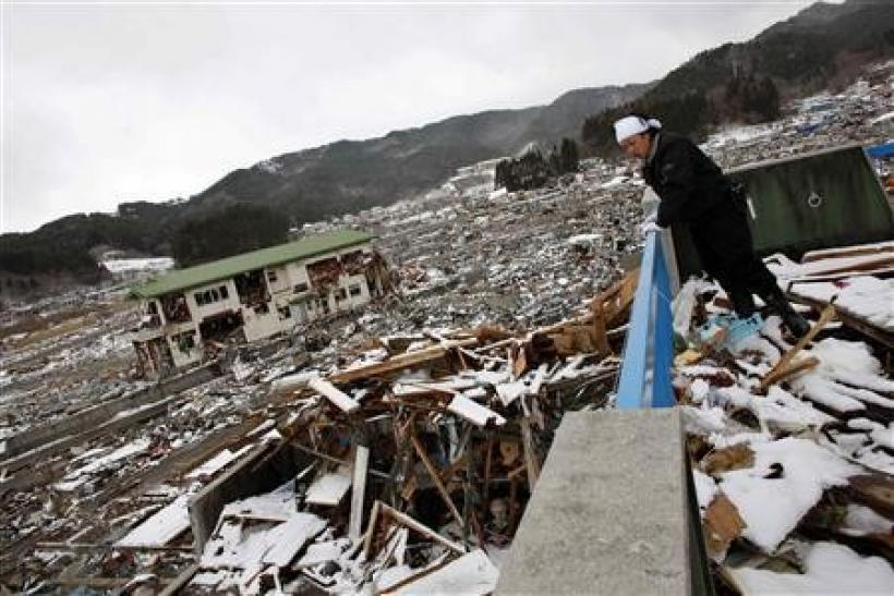 A survivor looks on at the debris from the second floor of his destroyed house in Yamada, Iwate Prefecture, days after the area was devastated by a magnitude 9.0 earthquake and tsunami, March 17, 2011