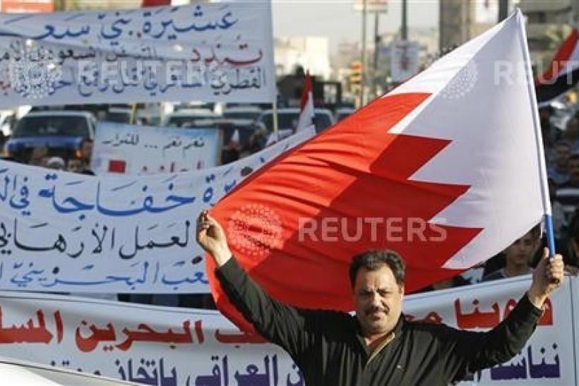 A resident holds up the Bahraini flag as he demonstrates in support of the Bahraini people in central Baghdad