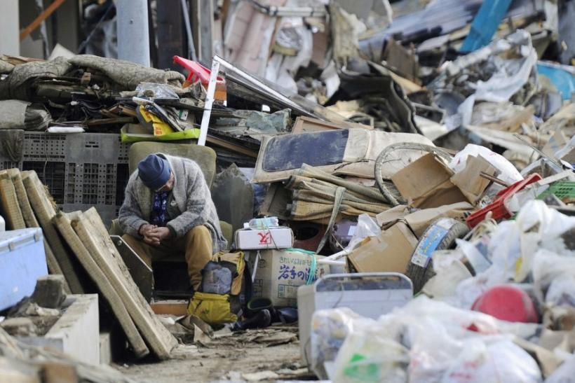 An elderly man sits on a chair among rubble in Kesennuma City