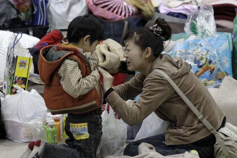 A mother touches her son's stomach at an evacuation center set in a gymnasium in Yamagata, northern Japan