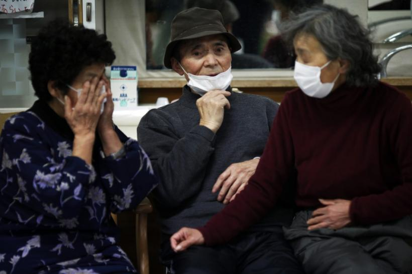 Elderly Japanese people are seen wearing face masks at a collective shelter for earthquake and tsunami survivors in Rikuzentakat