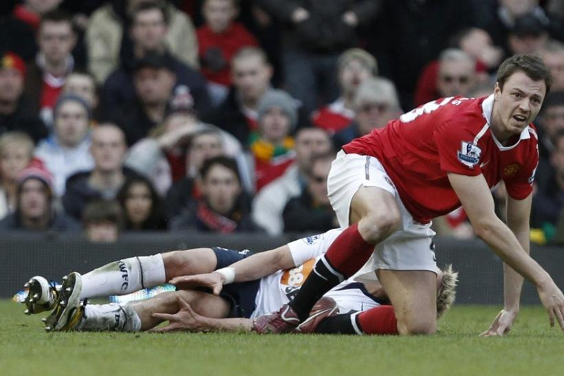 Manchester United's Evans reacts after a challenge on Bolton Wanderers' Holden during their English Premier League soccer match at Old Traffortd in Manchester.