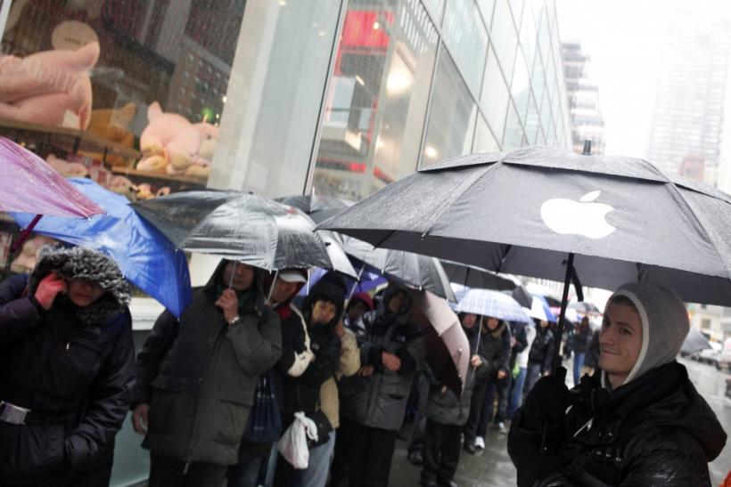 An employee (R) looks at customers stand in line outside Apple's flagship 5th Avenue store to purchase iPad 2 tablets in New York, March 16, 2011.