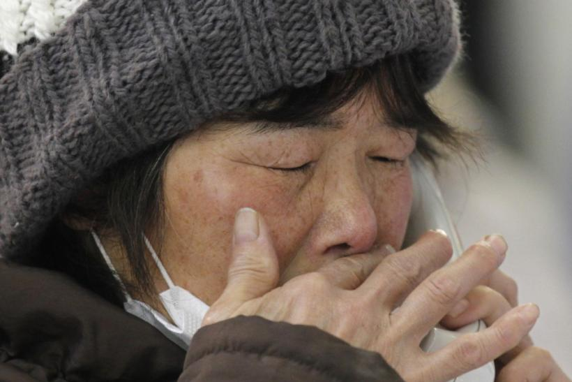 A woman cries as she talks with her relative on the phone at a temporary city hall office where people check the list of missing people and the dead in Kamaishi