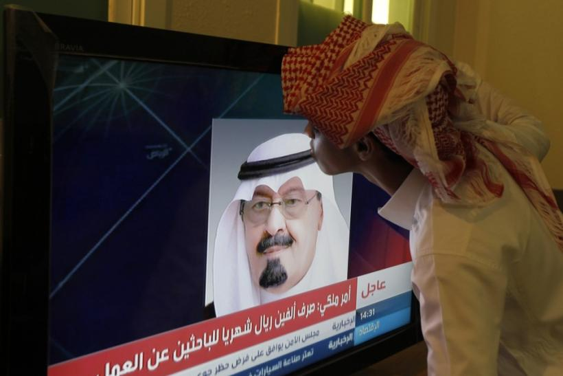 Ahmed Abdullah kisses a television screen showing an image of Saudi King Abdullah as he addressed the nation in Riyadh