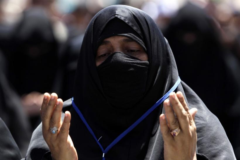 A woman recites prayers during a rally to demand the ouster of Yemen's President Ali Abdullah Saleh outside Sanaa