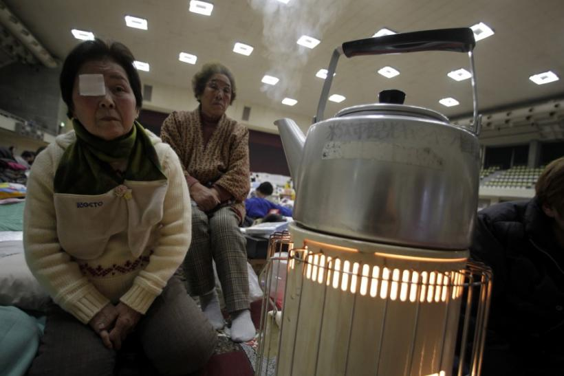 Suzuki and her friend Takahashi, who were evacuated from Minami Soma in Fukushima, sit next to a stove at an evacuation center in Yonezawa
