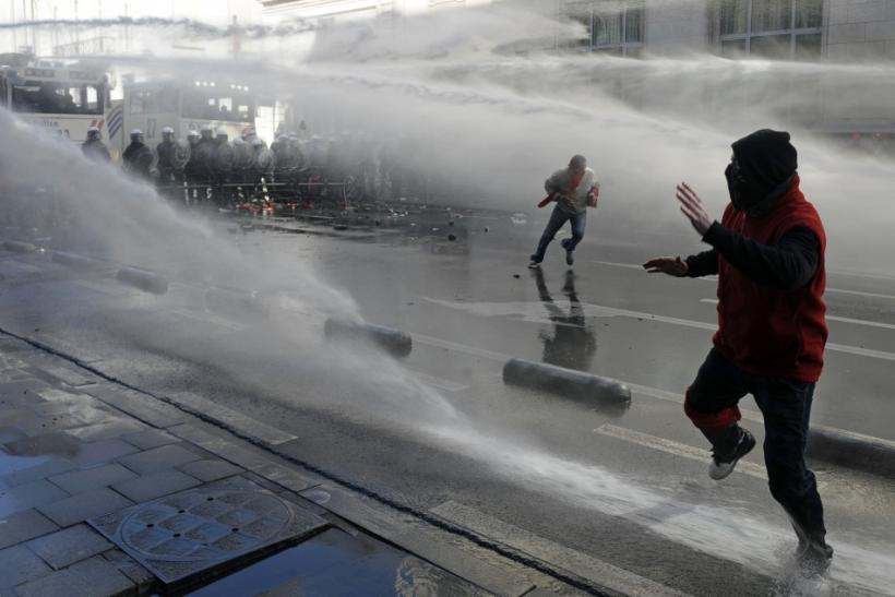 Demonstrators run while being sprayed by water canons during a protest in Brussels