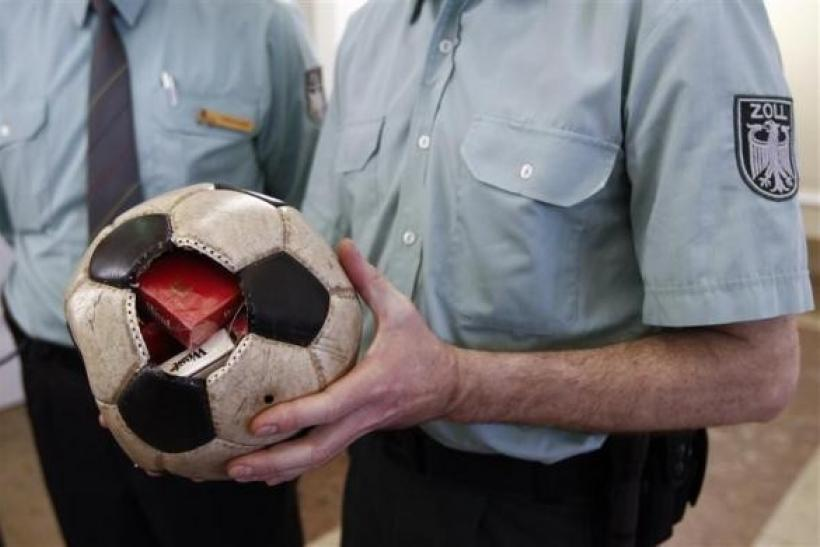A German customs officer holds a confiscated soccer ball