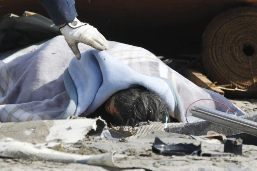 A police officer checks a dead body at a village destroyed by an earthquake and tsunami in Ofunato, northeast Japan