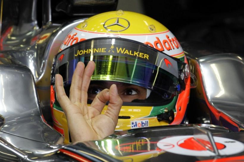 McLaren F1's Hamilton gestures from his car during the the first practice session of the Australian F1 Grand Prix in Melbourne.