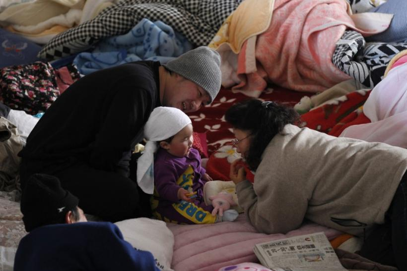 A toddler shares a light moment with her family at an evacuation centre in Yonezawa