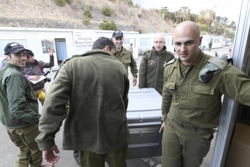 Israeli emergency medical team members carry equipment toward to their base in Minamisanriku town