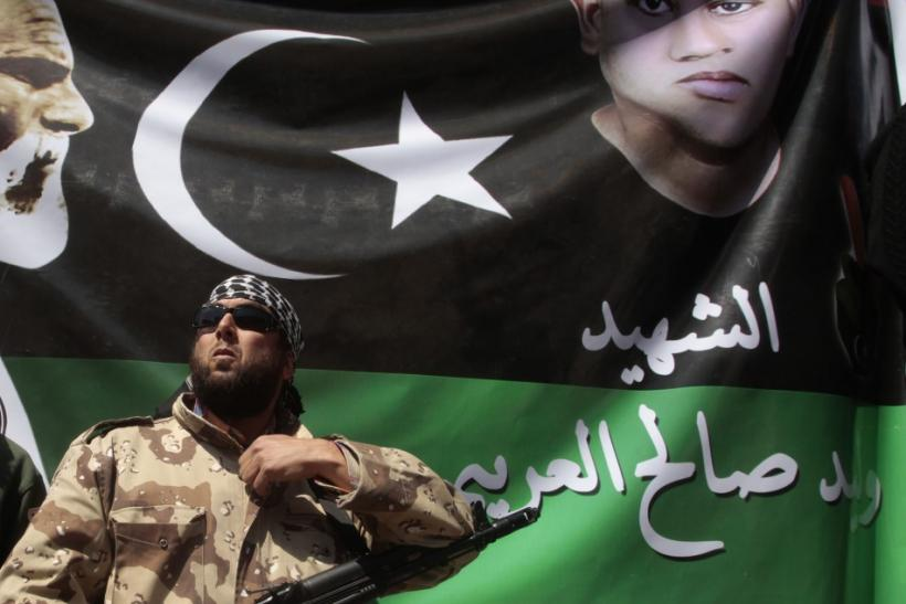 A rebel stands guard in front of a picture of a youth killed in the recent clashes, during Friday prayers in Benghazi