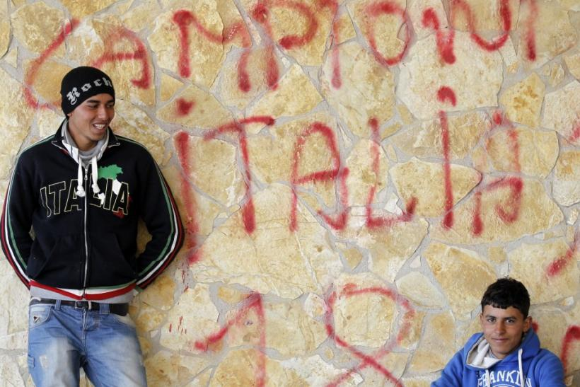 Two men fleeing the unrest in Tunisia rest after arriving at the southern Italian island of Lampedusa