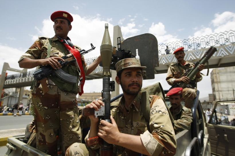 Army soldiers stand guard as anti-government protesters shout slogans at a barrier blocking a demonstration in Sanaa
