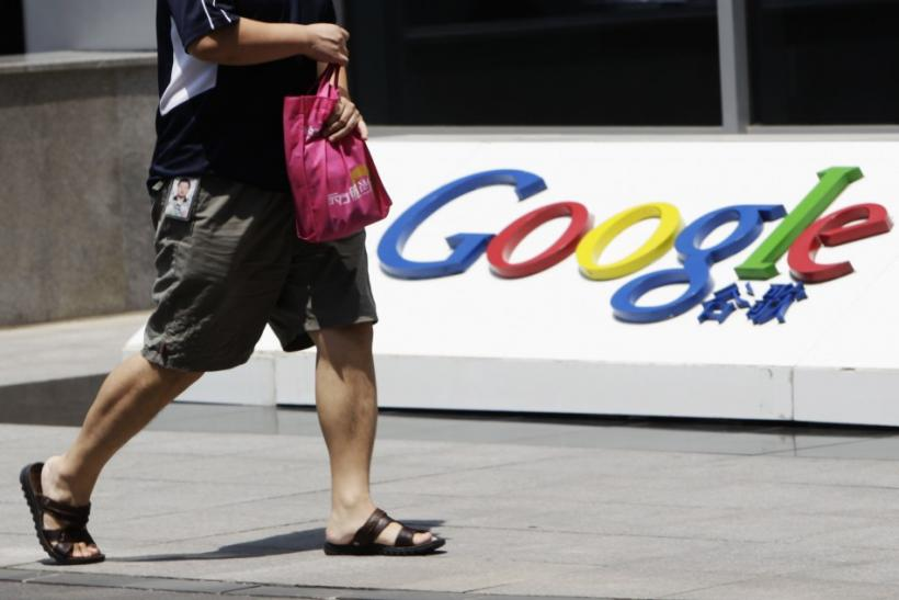 An employee walks past the logo of Google