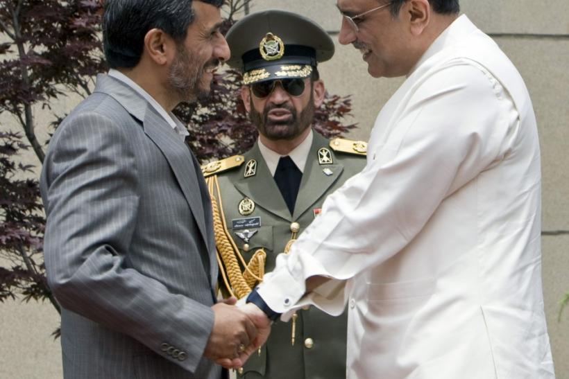 Iranian President Ahmadinejad greets Pakistan's President Zardari before the start of a trilateral summit in Tehran