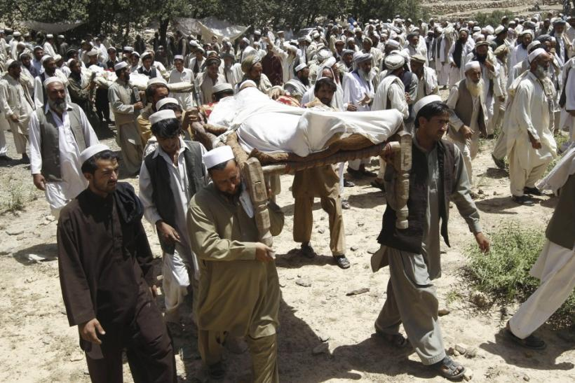 Afghan men carry bodies of people who were killed after insurgents attacked a wedding party in Dur Baba district