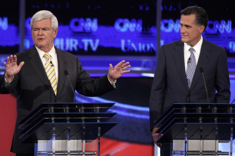 Former Speaker of the U.S. House of Representatives Newt Gingrich answers questions as former Massachusetts Governor Mitt Romney listens at the first New Hampshire debate of the 2012 campaign in Manchester, New Hampshire