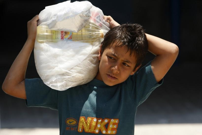 A Palestinian boy carries a sack of food supplies at a U.N food distribution Center in Gaza City