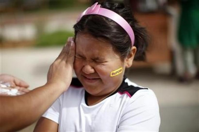 Fernanda Garcia-Villanueva, 8, has sunscreen applied before the annual run/walk for patients and their friends and families at The Children's Hospital